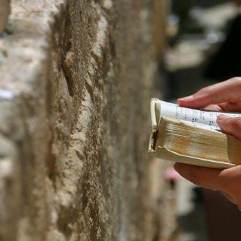 אדם מחזיק סידור תפילה ומתפלל שחרית בכותל המערבי