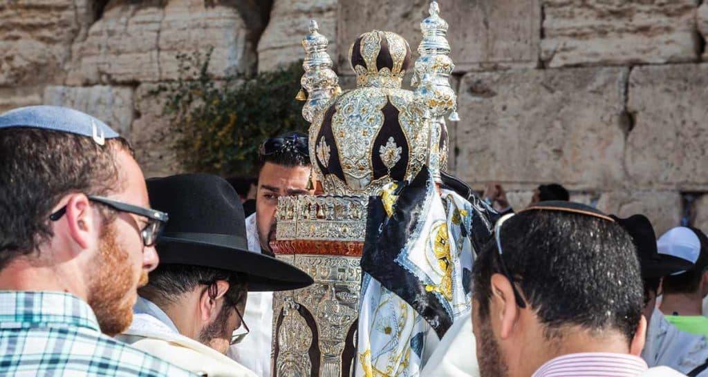 יהודים מתפללים ליד ספר תורה בכותל המערבי