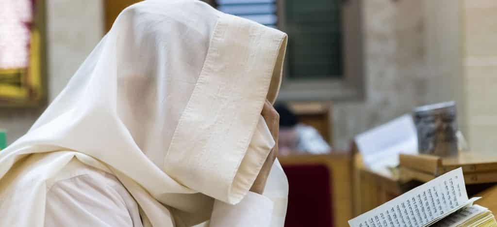 מתפלל בבית הכנסת מכסה את עיניו וקורא קריאת שמע