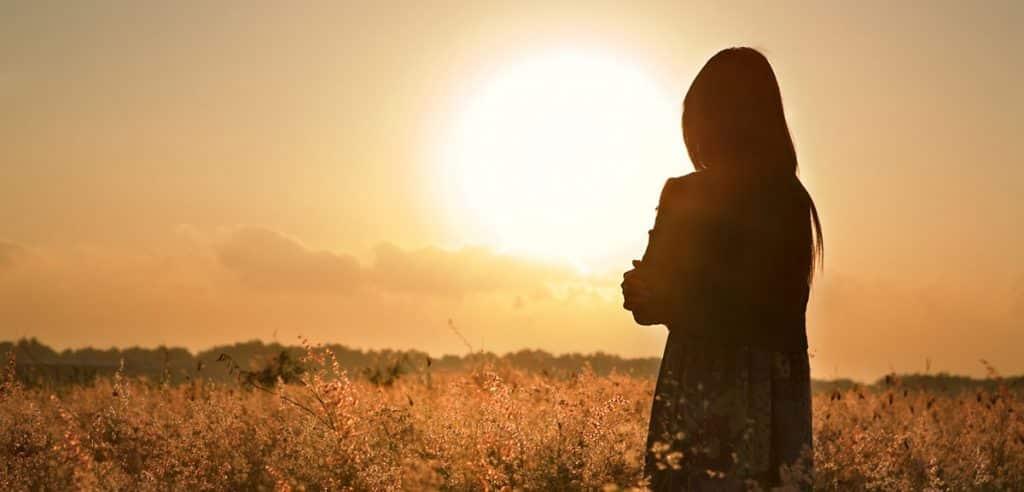 אישה עומדת בשדה מול השמש בשקיעה