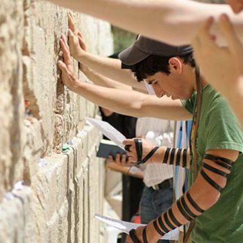 נער עם תפילין מתפלל תפילת שמונה עשרה בכותל המערבי